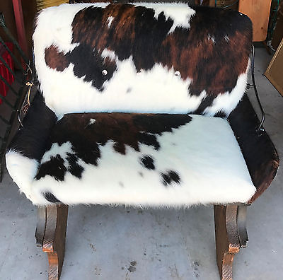 Vintage Buggy seat turned into a great 2 seat chair covered with cowhide.