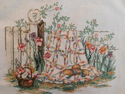 Completed finished cross stitch picture of quilt, fence, flowers