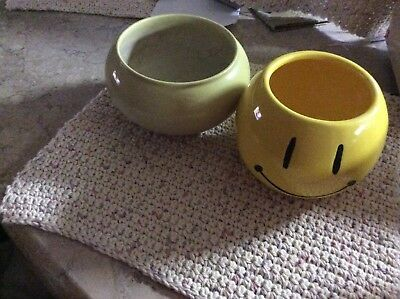 Two vases one has a smiley face and the other one is light green ( vintage. )