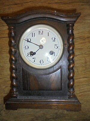 Edwardian oak mantel clock, with barley-twist supports and enamelled dial.
