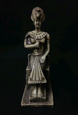 Ancient Egyptian statue of god Osiris holding crook wearing crown