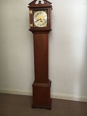 Granddaughter clock in dark wood with gold clock face and chimes