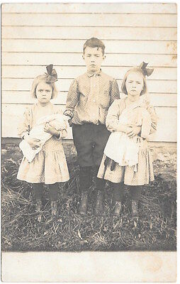 Real Photo Postcard Boy & Two Girls with Dolls Outside~101752