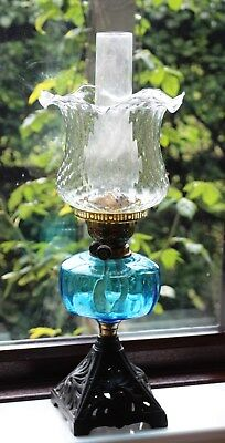 Early 20th century oil lamp with blue glass fount and cast iron base