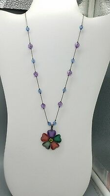 purple and blue beaded necklace on black chain with multi color flower pendant.