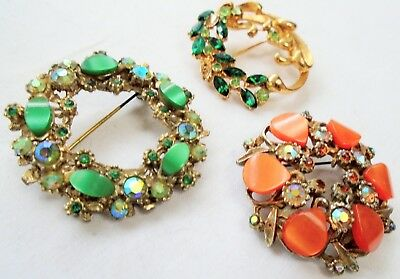 Three large vintage brooches (gold metal, emerald paste, a.b crystal etc)