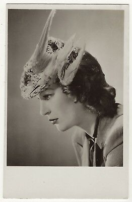 A Pretty Woman Wearing An Art Deco Hat Featuring A Decorative Real Bird