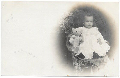 Real Photo Postcard Baby Holding a Teddy Bear in a Studio Wicker Chair~103958
