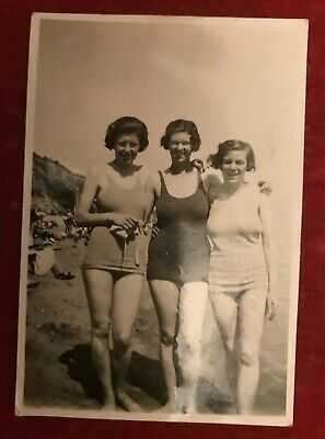 1930s photo of 3 x sisters at the beach in swimming costumes .