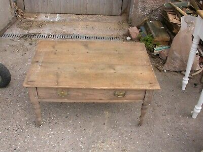 Antique pine coffee table with porcelain casters for restoration.