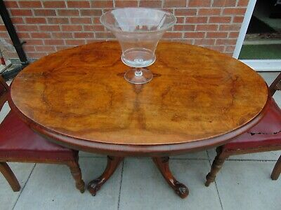 Oval burr walnut 19th century loo tilt top dining table with scrolled feet