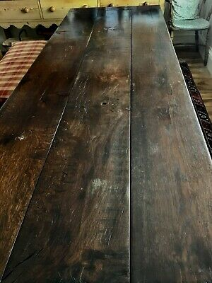 Large solid oak dining table with chunky legsand four benches with cushions.