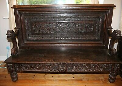 Antique Oak Settle With Carved Heads On Arms
