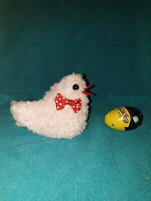 Hand knitted Easter chick egg cosy to cover a creme egg. Red dot bow