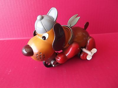 "WIND-UP PLASTIC DOG ON BIKE 6""IN LONG 4.5""IN TALL  WORKS GOOD"