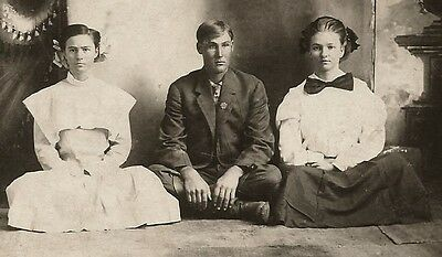 One Man and Two Women Sitting Cross Legged on the Floor 1900s RPPC