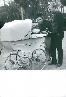 Vintage photo of Farah Pahlavi standing with a man and moving baby trolley. -