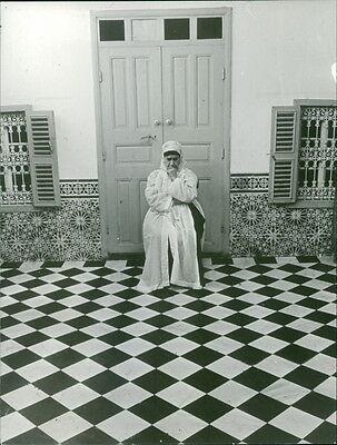 Vintage photo of A woman sitting in front of a close door contemplating.Taken