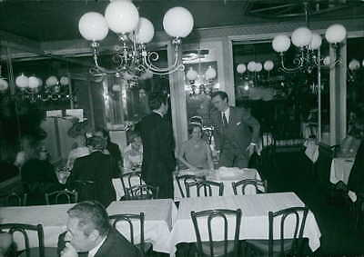 Vintage photo of Margrethe and Henrik of Denmark at table in restaurant. -