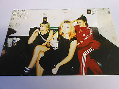 SPICE GIRLS  photo three of the girls sat on sofa one having a drink of water