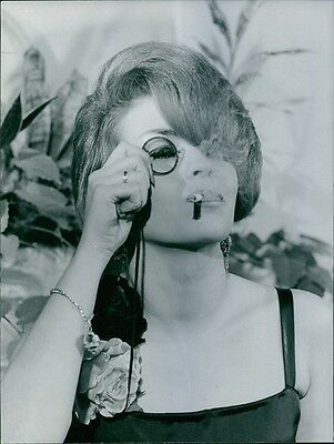 Vintage photo of The lady is holding a single eye glass while smoking.1964