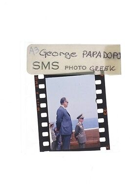 Slide of Georgios Papadopoulos standing with the officer during an event.