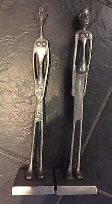 Pair of naive cast aluminium elongated female african? figures