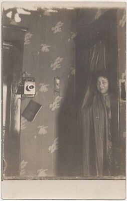 Great RPPC: woman hiding behind curtain, 1910s
