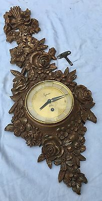 A Vintage gilded Syroco Gilded Wall Clock 8day Jewelled Movement U S A