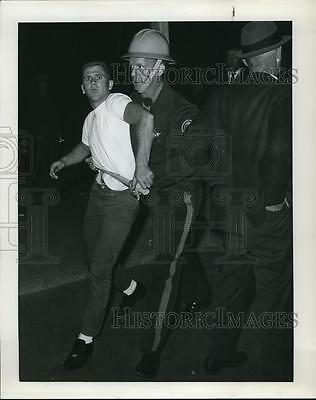 1964 Press Photo Young man escorted by State Police officer Seaside Riot