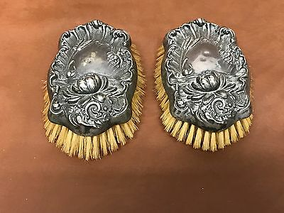 ONE PAIR ANTIQUE ART NOUVEAU STERLING PLATED HANDLE REPOUSSE BRUSHES . Plated