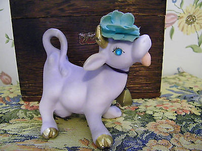 porcelain purple cow with gold trim, bell, and flower on her head