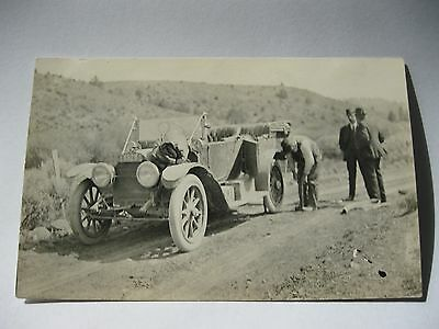 divided black and white Azo RPPC featuring CHANGING A FLAT ON AN ANTIQUE CAR