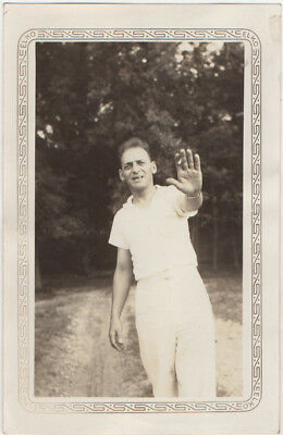 Snaggle-toothed man holds up warning hand (with cig) to photographer, 1930s