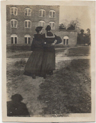 Backs of 2 affectionate women, with shadow of woman photographer, 1900s