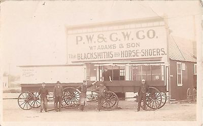 c.1910 RPPC PW & CW Co. Wm. Adams & Son Blacksmiths & HorseShoers Store & Wagons