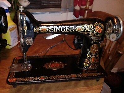 """Vintage """"Red Eye"""" Singer sewing machine with a light, parts and supplies."""