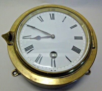 Antique brass cased bulk head clock with whit enamel dial