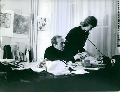 Vintage photo of Jacques Esterel in his office with a woman taking phone call. P