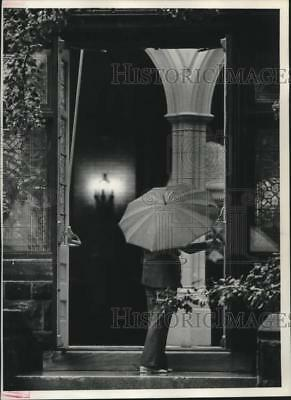 1977 Press Photo A woman with an umbrella watches services for Alfred Lunt
