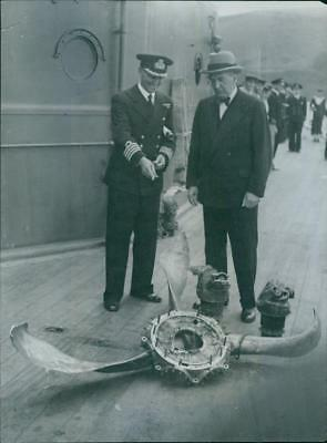 Captain J. Armstrong show Mr. SM Bruce Australian high commissioner a propeller
