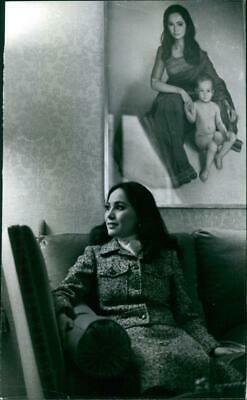 Dewi Sukarno siting on the sofa in home beside her photograph on the wall. - Vin