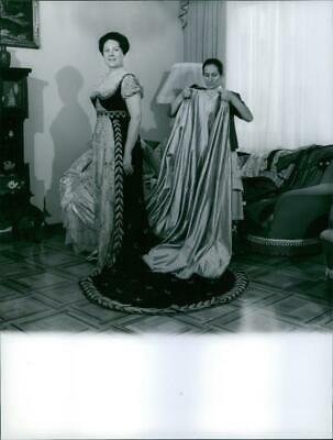 Renata Tebaldi getting help to get dressed from a lady. - Vintage photo