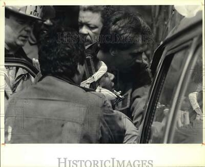 1991 Press Photo Members of the Syracuse Fire Department extricate Juan Taylor