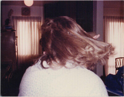 Back of a woman, hair swirling, 1980s