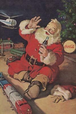 1962 COCA-COLA SANTA SITTING WITH COKE TRAIN HELICOPTER UNDER TREE AD PRINT H938