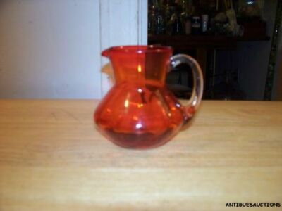 VINTAGE AMBER/RED PILGRAM PITCHER WITH A CLEAR GLASS HANDLE