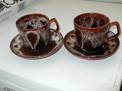 TWO STUDIO WARE CUPS AND SAUCERS  BELIEVED TO BE FOSTERS OF CORNWALL