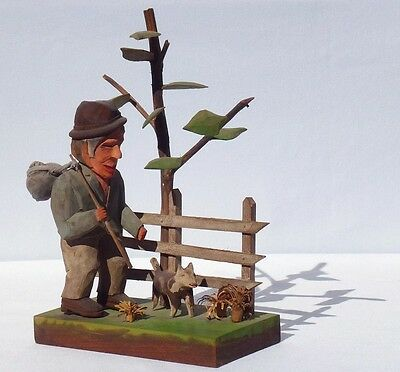 A Carving by Kentucky folk artist Unto Jarvi of a man walking with a dog.