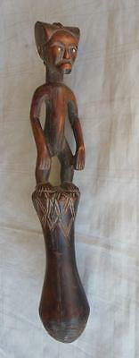 Tanzania carved Food pounder standing figure of a pouting child atop long beater